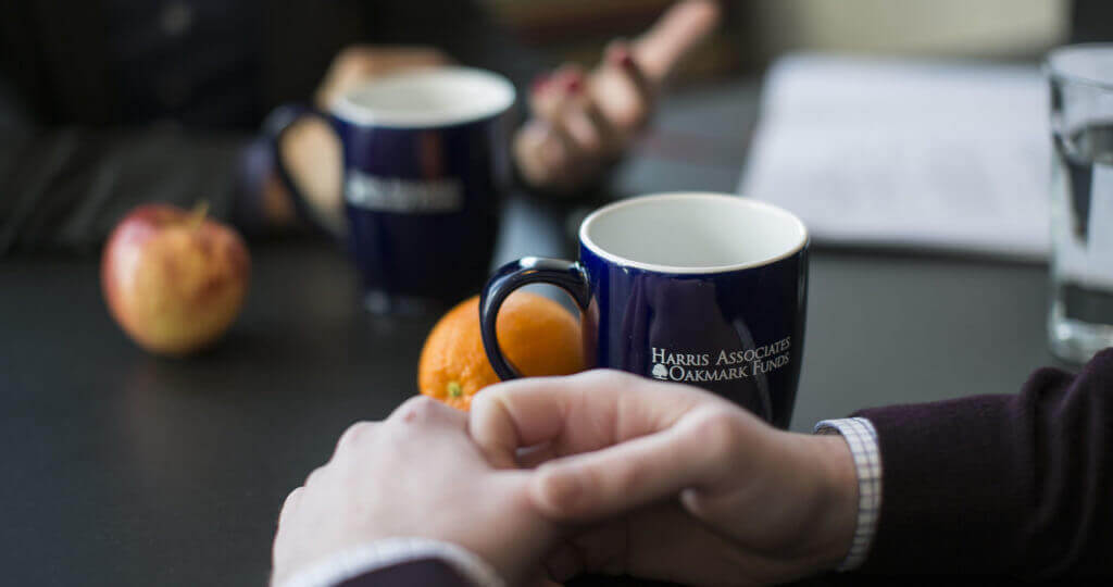 Hands on a table with oranges and a Harris-Oakmark coffee mug