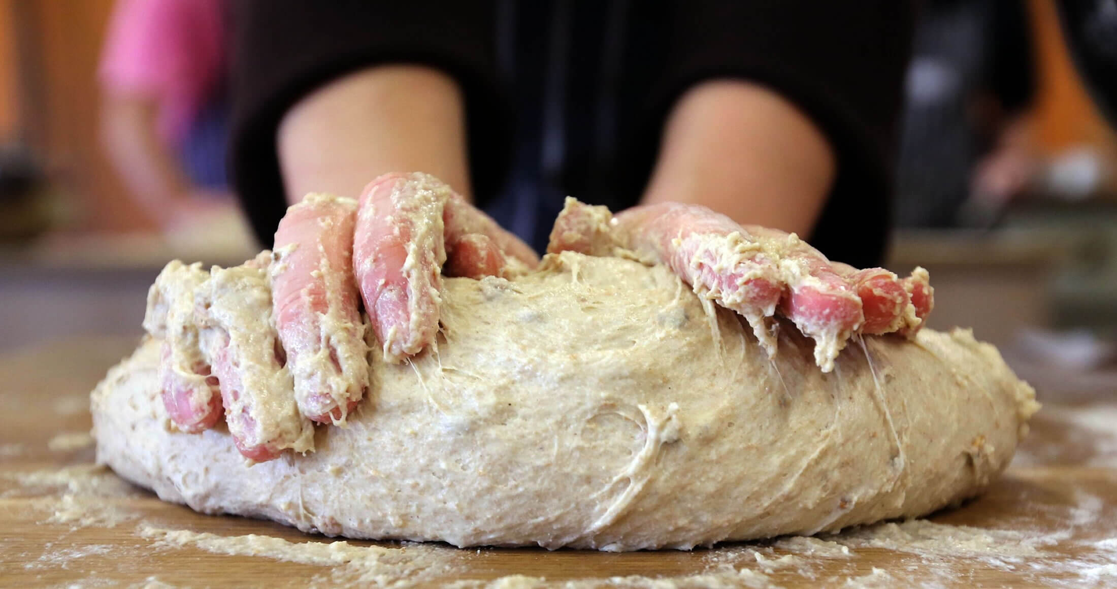 Image of hands covered in dough making bread